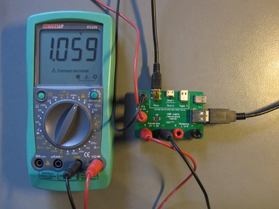 USB cable tester connected to a multimeter.