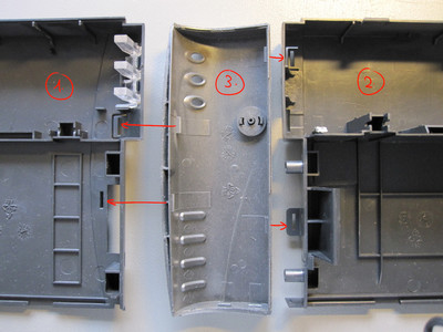 Parts of the plastic enclosure with marked latches.